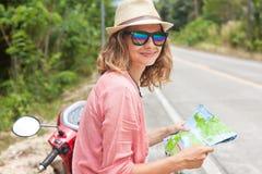 有地图的美丽的少妇在手中和在ro的一辆摩托车 库存照片