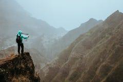 有地图的远足者在高山前面一个难以置信的全景视图的陡峭的岩石地形排列深山沟和 图库摄影