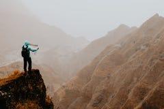 有地图的远足者在高山前面一个难以置信的全景视图的陡峭的岩石地形排列深山沟和 库存照片