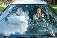 有地图驾驶的妇女的人 免版税库存照片