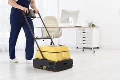 有地板清洁机器的男性工作者 免版税库存图片