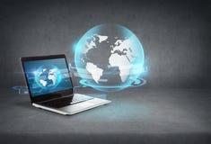 有地球全息图的便携式计算机在屏幕上 免版税库存照片