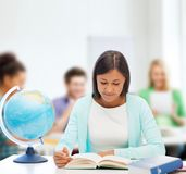 有地球和书的老师在学校 免版税库存照片