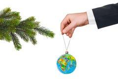 有地球和圣诞树的手 免版税库存照片