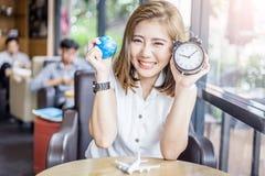 有地球和闹钟的逗人喜爱的微笑的亚洲女孩 图库摄影