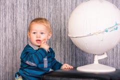 有地球的可爱的好奇男婴 免版税库存照片