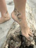 有地球的地图的脚腕纹身花刺的一个女孩在桑迪日志站立 库存照片