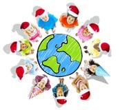 戴有地球的小组孩子圣诞节帽子 免版税库存图片