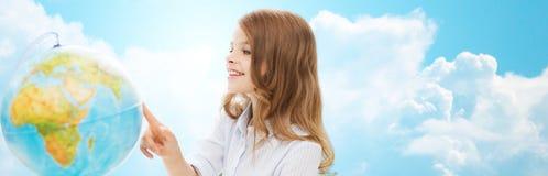 有地球的微笑的学生女孩在学校 免版税图库摄影