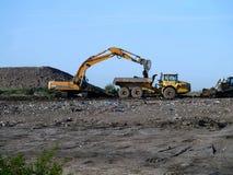有地球的挖掘机的装货倾销者卡车 免版税图库摄影