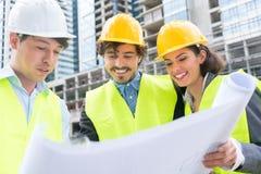 有地面推算标绘图的建筑师在建造场所 免版税库存图片