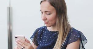 有坐一个开放阳台和写消息的长发的年轻女人在一个手机 影视素材