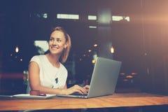 有坐与在咖啡店的便携式的网书的美好的微笑的可爱的女性 免版税库存照片