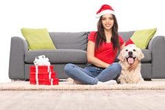 有坐与她的狗的圣诞老人帽子的女孩 库存图片
