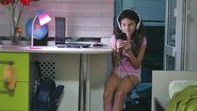 有坐与戏剧智能手机的耳机的十几岁的女孩 打在户内智能手机的女小学生女孩网络游戏 股票视频