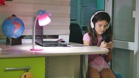 有坐与戏剧智能手机的耳机的十几岁的女孩 打在户内智能手机的女小学生女孩网络游戏 股票录像