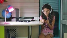 有坐与戏剧智能手机的耳机的十几岁的女孩 打在智能手机互联网上的女小学生女孩网络游戏 股票视频
