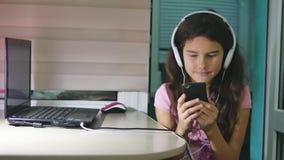 有坐与戏剧智能手机的耳机的十几岁的女孩 打在智能手机互联网上的女小学生女孩网络游戏 股票录像