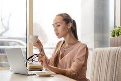 有坐在一个咖啡馆的一张桌上的长的头发的苗条时髦的年轻可爱的企业夫人博客作者与膝上型计算机和咖啡杯 库存图片