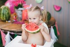 有坐在一张高脚椅子和吃切片一个水多的西瓜的尾巴的逗人喜爱的白肤金发的女孩在夏天 免版税库存照片