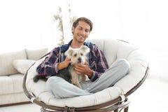 有坐在一把大扶手椅子的狗的英俊的人 库存照片