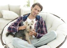 有坐在一把大扶手椅子的狗的英俊的人 库存图片
