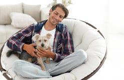 有坐在一把大扶手椅子的狗的英俊的人 免版税图库摄影
