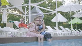 有坐在与他们的脚的水池边缘的猪尾和成熟妇女的逗人喜爱的矮小的滑稽的女孩水一会儿 影视素材