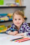 有坐在与多彩多姿的铅笔的桌上和看照相机的金发的可爱的微笑的小女孩 库存图片
