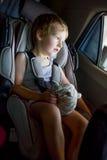 有坐在与玩具的一个儿童汽车座椅的明亮的头发的男婴在手上 免版税库存照片