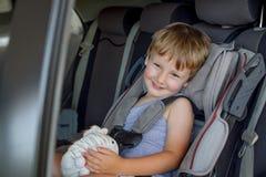 有坐在与玩具的一个儿童汽车座椅的明亮的头发的男婴在手上 免版税图库摄影
