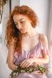 有坐在与花的窗口,春天心情的红色头发的美女 库存图片