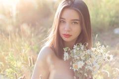有坐在与雏菊花束的一个领域的充分的嘴唇的美丽的甜女孩与obnozhennymi的担负在sunl的日落 免版税库存图片