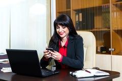 有坐在书桌的一个手机的少妇 免版税库存图片