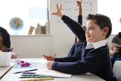 有坐在书桌的唐氏综合症的男小学生举他的在小学类,关闭的手,侧视图 库存图片