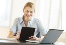 有坐在书桌的数字式片剂和膝上型计算机的女实业家 图库摄影