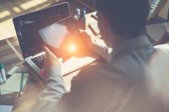 有坐在他的书桌的片剂计算机和膝上型计算机的经理 在表上的文书工作 库存图片