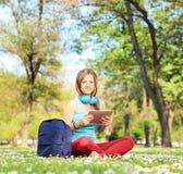 有坐在公园的耳机和片剂的年轻女学生 免版税库存照片