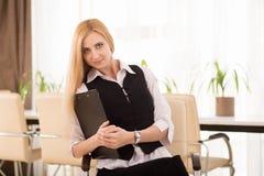 有坐在办公室的剪贴板的可爱的女实业家 免版税库存图片