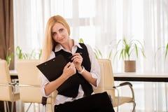 有坐在办公室的剪贴板的可爱的女实业家 免版税库存照片