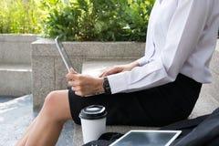 有坐在办公楼之外的膝上型计算机的女实业家 年轻 免版税库存图片