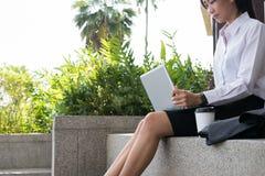 有坐在办公楼之外的膝上型计算机的女实业家 年轻 图库摄影