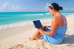 有坐在加勒比海的膝上型计算机的妇女 免版税库存图片