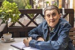 有坐在咖啡馆和写在笔记本的伤残的人们 免版税库存图片