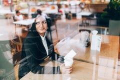 有坐在咖啡馆的巧妙的电话的女商人 免版税库存照片