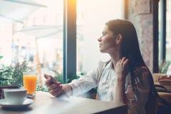 有坐在咖啡馆的手机的妇女,读从网络的新闻 免版税库存图片