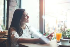 有坐在咖啡馆的手机的英俊的微笑的妇女,读从网络的愉快的新闻 库存图片
