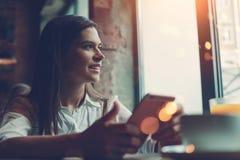有坐在咖啡馆,午餐闸和检查社会网络新闻组的手机的英俊的妇女 免版税库存图片