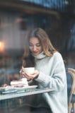 有坐在咖啡馆, drin的棕色长的头发的美丽的少妇 免版税库存图片