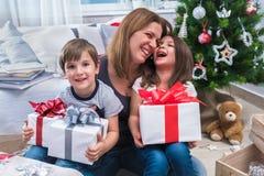 有坐在圣诞树前面的两个孩子的微笑的母亲为假日做准备 库存照片